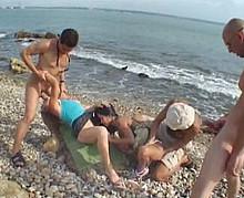 deux couples échangistes sur une plage naturiste